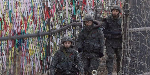 South Korean army soldiers patrol by ribbons, wishing for the reunification of the two Koreas, attached...