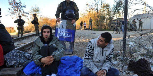 Migrants and refugees blockade railroad tracks as they wait to cross the Greece-Macedonia border, near...