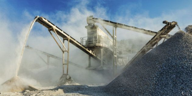 Industrial background - crusher rock stone crushing machine at open pit mining and processing plant for...