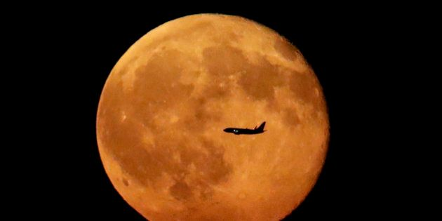 A plane flies in front of the moon rising in its waning period seen from Eagle Rock Reservation, Wednesday,...
