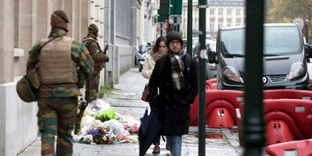Belgian Army soldiers patrol next to flowers left outside of the French Consulates office in Brussels...