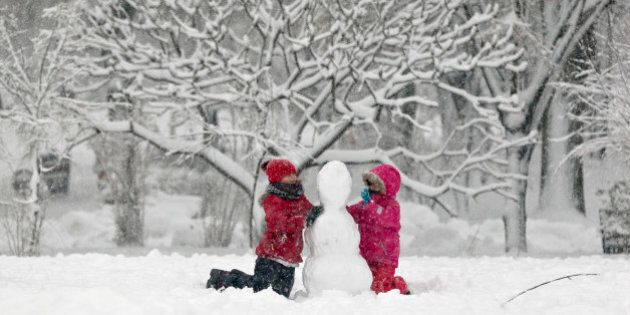 Children build a snowman in a park in Bucharest, Romania, Monday, Dec. 29, 2014. Romania, especially...