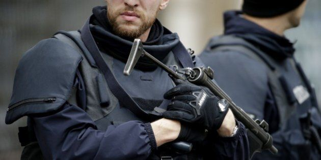 Armed Police officers man a cordon around a car in the 18th district of Paris on November 17, 2015 which...