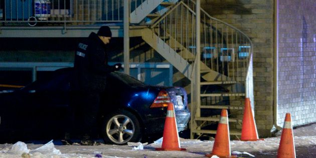 Police search a vehicle near the scene of a murder in the neighbourhood of Notre Dame de Grace, in Montreal,...