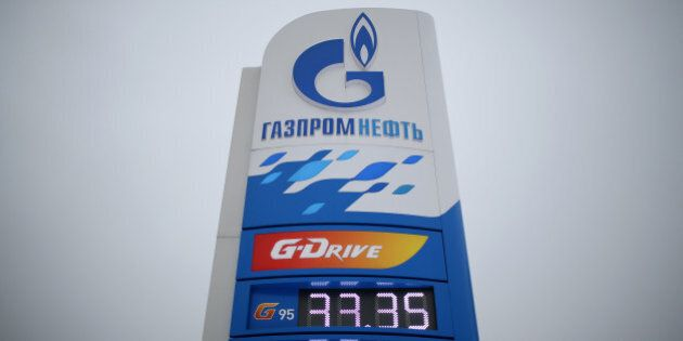 Fuel price signs stand on display at a gas station operated by OAO Gazprom Neft in Moscow, Russia, on...