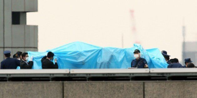 Japanese policemen cover with a blue sheet and inspect a small drone, which was found on the roof of...