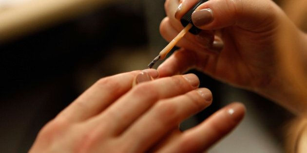 NEW YORK, NY - SEPTEMBER 08: A manicurist paints a models nails backstage at the Band of Outsiders Spring...