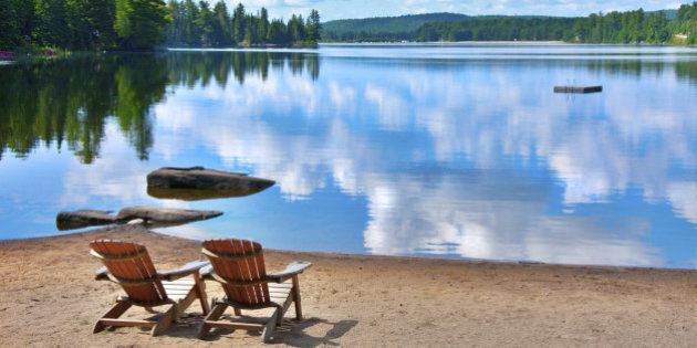 two wooden deck chairs on the shore of a lake in Canada with clouds reflecting on the