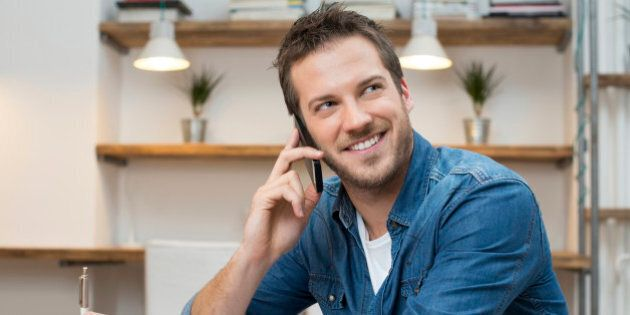 Portrait of young businessman talking on mobile phone in office