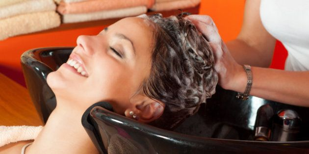 Beautiful young girl enjoying hair washing in hairdressing salon.