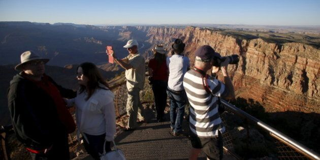 People take photos as the sun sets at the Grand Canyon National Park in northern Arizona, April 13, 2015....