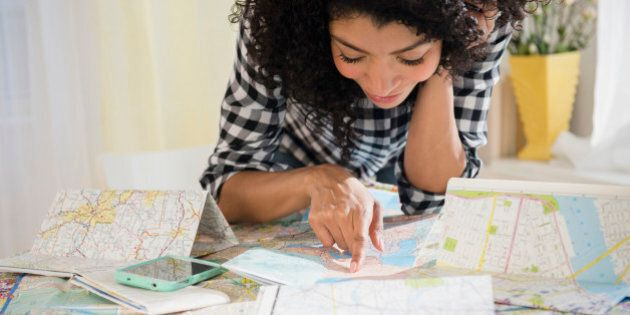 Mixed race woman planning road trip with