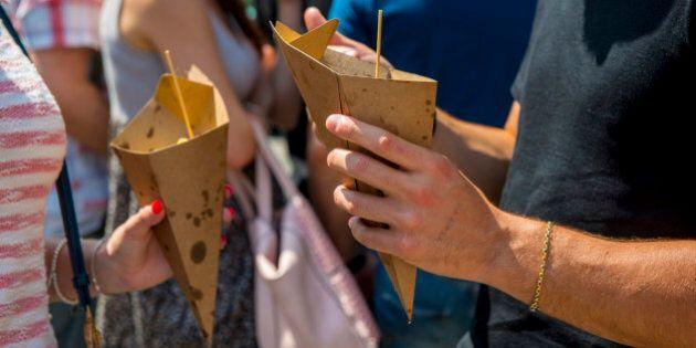 people enjoy street food from paper
