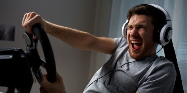 technology, gaming, entertainment and people concept - young man in headphones with pc computer playing...
