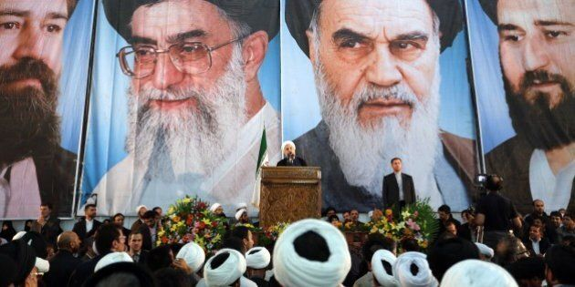 Iranian President Hassan Rouhani delivers a speech under portraits of Iran's supreme leader, Ayatollah...