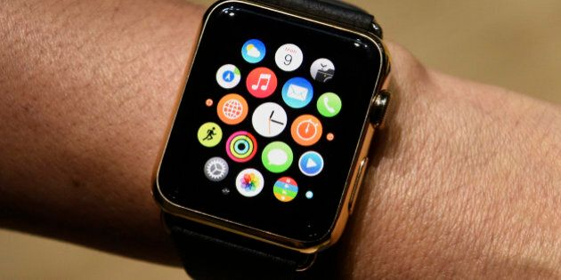 An attendee displays the Apple Watch Edition for a photograph during the Apple Inc. Spring Forward event...