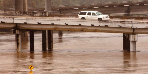 A SUV drives over flooded White Oak Bayou in Houston, Texas October 25, 2015. Precipitation was expected...