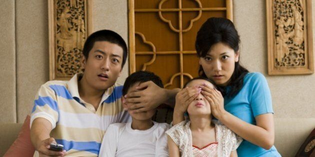 Family watching television with parents covering children's