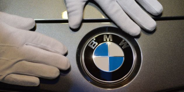A man with white gloves cleans a logo of car manufacturer BMW prior to the annual balance press conference...