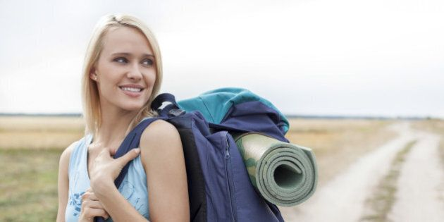 Beautiful woman with backpack looking away while hiking at