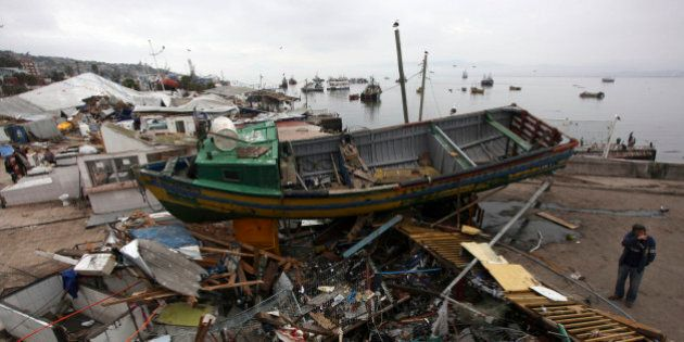 A man stands near a fishing boat that was lifted by an earthquake-triggered tsunami, in Coquimbo, Chile,...