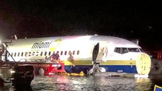 In this photo released by the Jacksonville Sheriff's Office, authorities work at the scene of a plane in the water in Jacksonville, Fla., Friday, May 3, 2019. Officials say a charter plane traveling from Cuba to north Florida ended up in a river at the end of a runway. A Naval Air Station Jacksonville news release says a Boeing 737 arriving from Naval Station Guantanamo Bay, Cuba, crashed into the St. Johns River Friday night. (Jacksonville Sheriff's Office via AP)