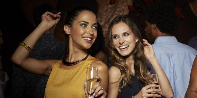 Cheerful female friends dancing while having champagne in nightclub