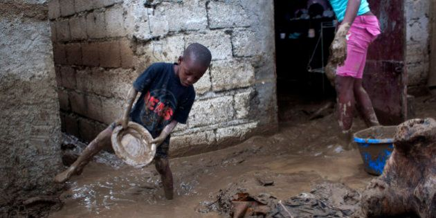 Winsky Pierre, left, 5, helps to drain mud from his flooded house after the passing of Tropical Storm...