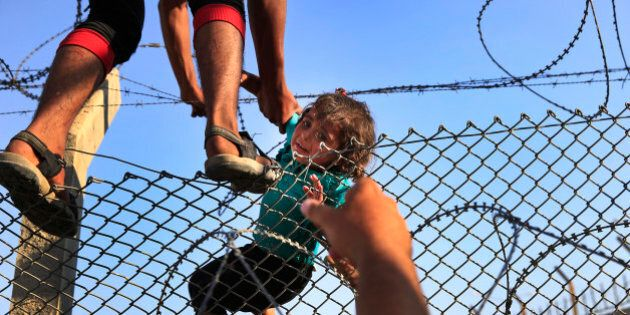 FILE - In this June 14, 2015 file photo, a Syrian refugee lifts a baby over the border fence into Turkey...