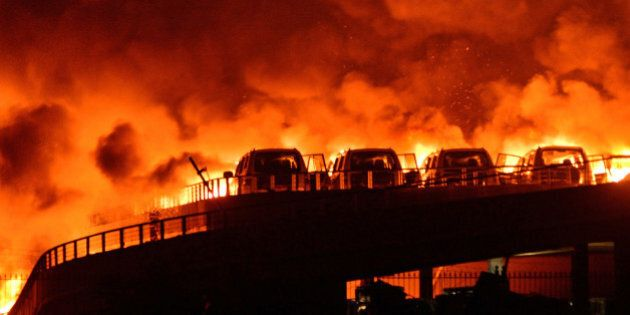 TIANJIN, CHINA - AUGUST 13: (CHINA OUT) Fire and smoke are seen after explosions at a warehouse on late...
