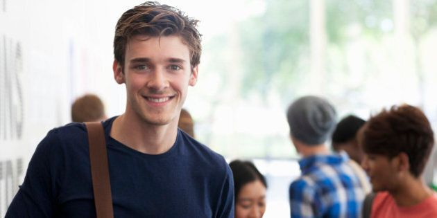 Portrait of smiling university student standing in corridor during break, people in background talking
