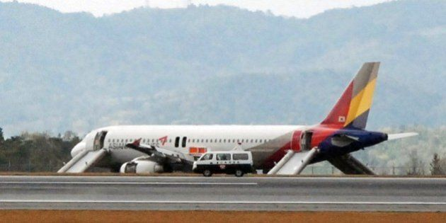 An Asiana Airlines Airbus A320 aircraft is seen with its evacuation slides deployed after it overran...