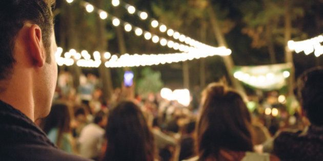 Back view of young man sitting and enjoying in a open night music festival outdoors on