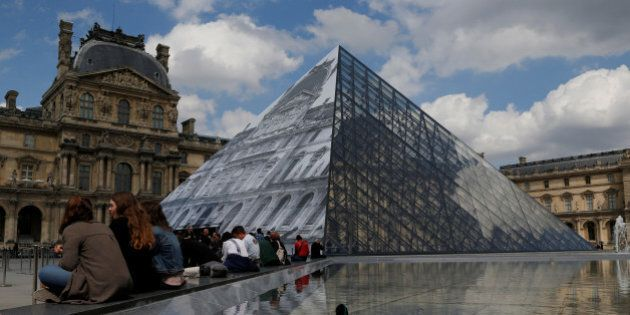 Vistors sit beside a reflecting pool near French artist JR's lastest work, an image of the facade of...