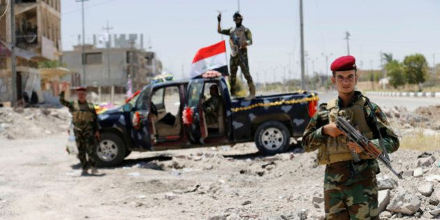 Iraqi government forces react to the camera in Falluja after government forces recaptured the city from...