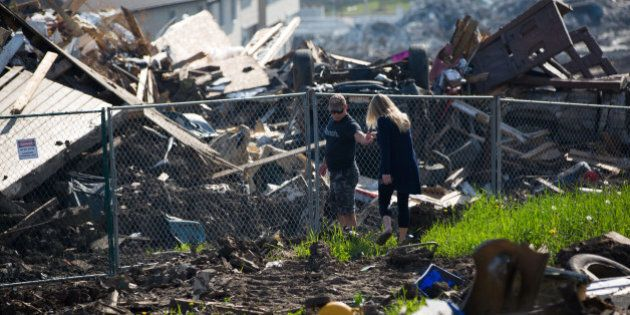 Residents look over the damage in the Timberlea neighbourhood as thousands of evacuees who fled a massive...