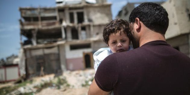 A Palestinian man carrying a child walks past buildings destroyed during the 50-day war between Israel...