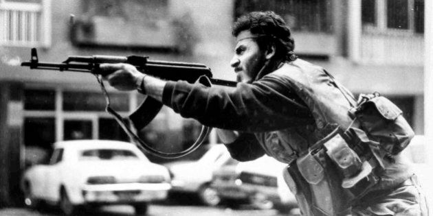 FILE - In this Feb. 20, 1987, file photo, a Shiite Muslim AMAL militiaman fires his AK-47 assault rifle...