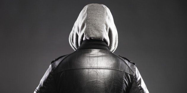 Young man in leather jacket and hood rear view on