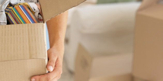Close-up of a young man's hand holding a cardboard box