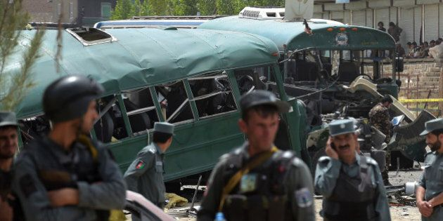 TOPSHOT - Afghan security personnel gather near the wreckage of buses which were carrying police cadets,...