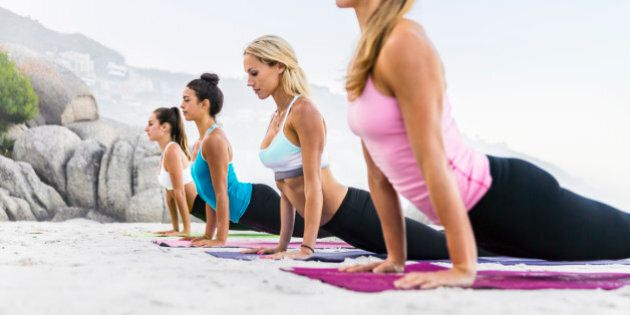 Women focusing on healthy exercise by the sea on a sandy beach while doing physical, mental, and spiritual...