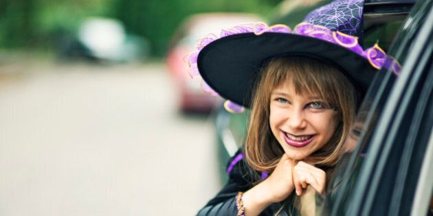 Portrait of a little girl during halloween dressed up as a witch. The girl is aged 9 and is smiling from...