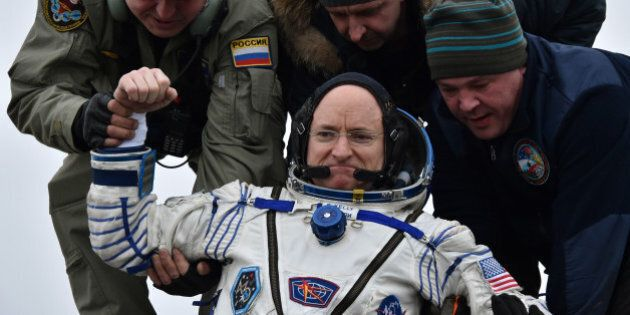 Ground personnel help International Space Station (ISS) crew member Scott Kelly of the U.S. to get off...