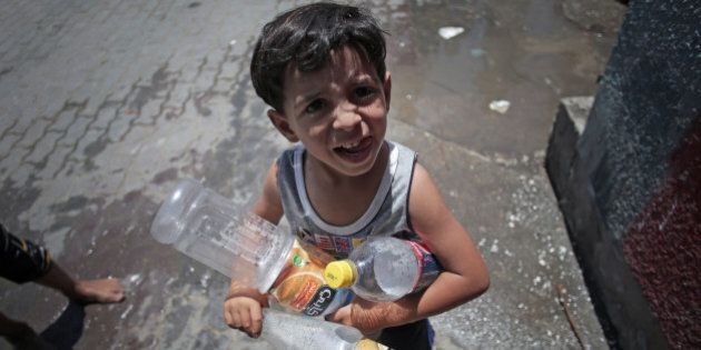 In this Monday, July 14, 2014 photo, a boy waits to fill empty bottles with water at the Gaza Boys United...