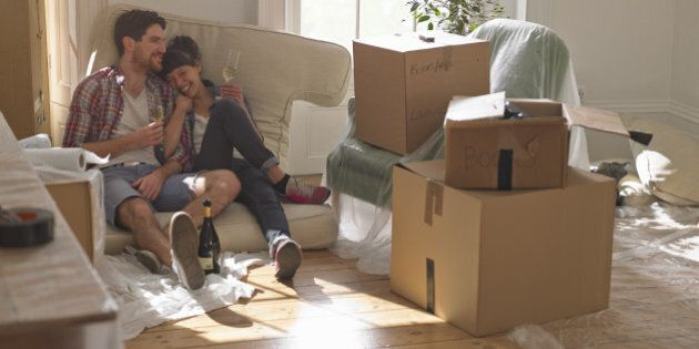 A young professional couple sitting on sofa cushions in their new house surrounded by packing boxes....