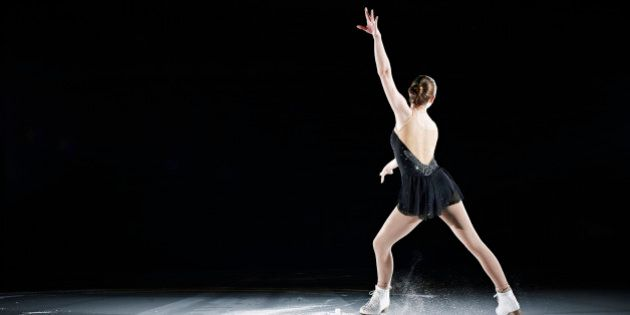 Female figure skater performing on ice rink in arena rear view