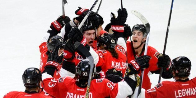 Ottawa Senators' Mark Stone (61) (centre) is surrounded by his teammates after scoring the game winning goal against the Pittsburgh Penguins during overtime NHL action in Ottawa on Tuesday April 7, 2015, in Ottawa. The Senators defeated the Penguins 4-3. THE CANADIAN PRESS/Justin Tang