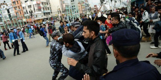 Nepalese police push back residents who began protesting after waiting for hours in line to board buses...