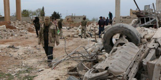 Rebel fighters walk through the rubble following an alleged bombing by Islamic State (IS) group in Marea,...